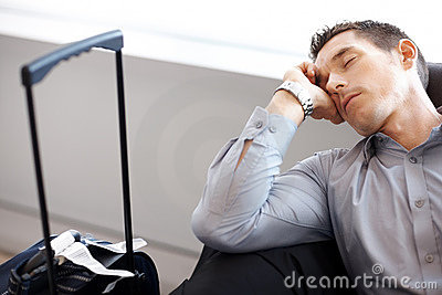 Young man sleeping at the airport lounge