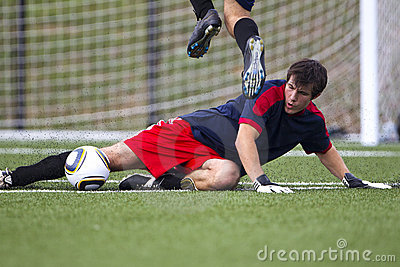 A young man slide kicks a soccer ball