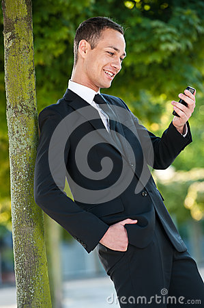 Young Man Smiling at his Phone in Park