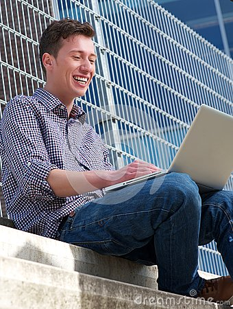 Young man smiling at laptop outdoors