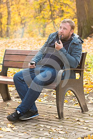 Free Young Man Smokes Tobacco Pipe In Park Royalty Free Stock Photos - 102040138