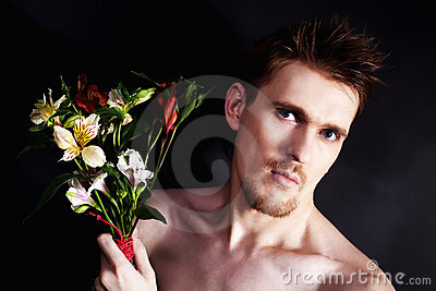 Young man sniffing bouquet of flowers closeup