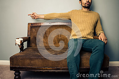 Young man on sofa pointing left