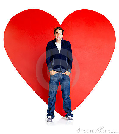 Young man standing against a big red heart