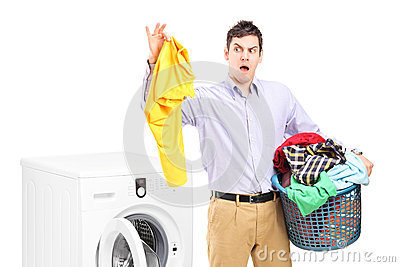 Young man standing next to a washing machine