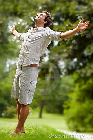 Young man standing in a park with hands outstretch