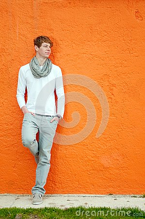 Young man standing by the wall