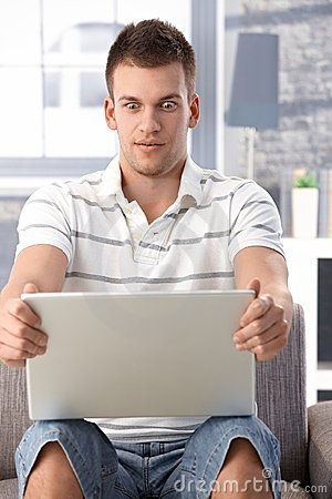 Young man staring at laptop screen horrified