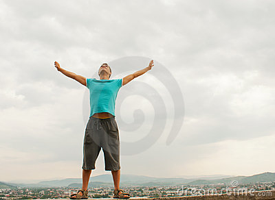 Young man staying with raised hands