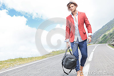 Young man strolls outside with bag