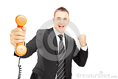 Young man in suit holding a telephone tube and smiling