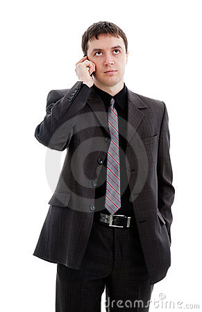 A young man in a suit, talking on the phone.