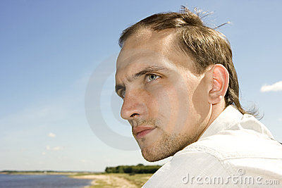 The young man in the summer on river bank