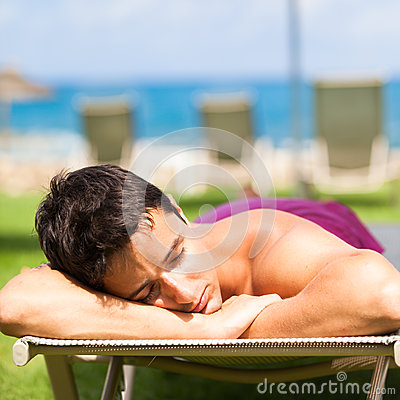 young man sunbathing and relaxing on a deckchair