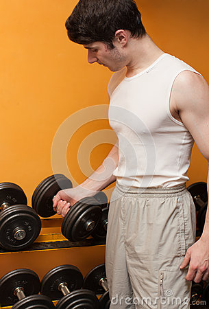 Young man take dumbbells in sport club