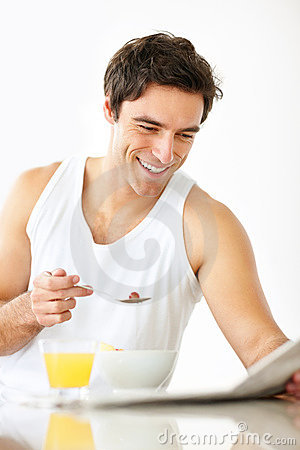 Young man taking breakfast while reading newspaper