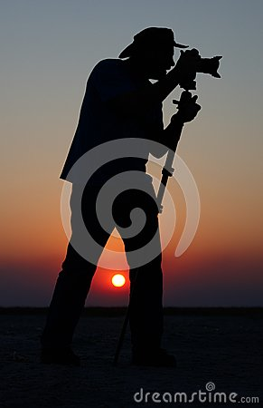 Young man taking pictures at sunset