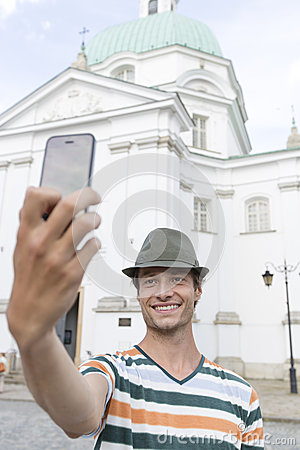 Young man taking self portrait outside St. Casimir Church, Warsaw, Poland