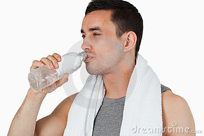 Young man taking a sip of water after workout