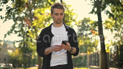 Young man taking smartphone from pocket and texting. Caucasian young man walking in the street, taking smartphone from his pocket and starting to text. Tracking stock video footage