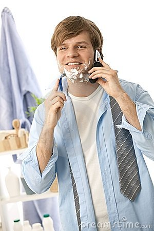 Young man talking on mobile while shaving