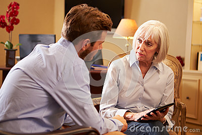 Young Man Talking To Counsellor Using Digital Tablet