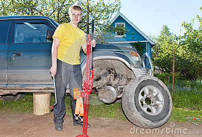 The young man, the teenager replaces a wheel at an off-road car