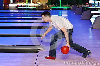 Young man throws ball in bowling