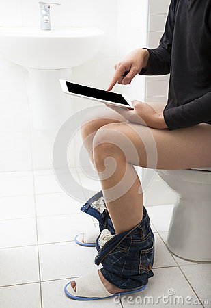 Young man in toilet using tablet