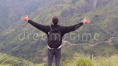 Young man tourist with backpack standing on the edge of beautiful canyon and victoriously raised hands. Male hiker. Reaching up top of mountain and stock video