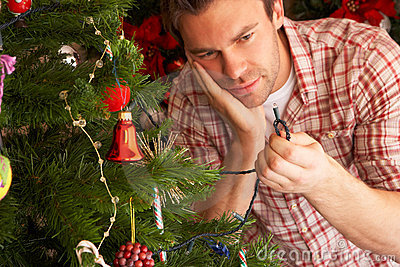 Young man trying to fix Christmas tree lights