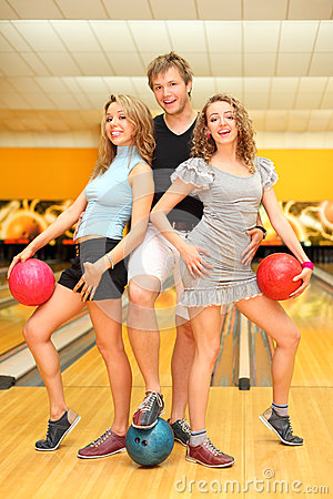 Young man and two girls hold balls in bowling club