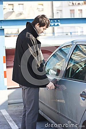 Young man unlocking car