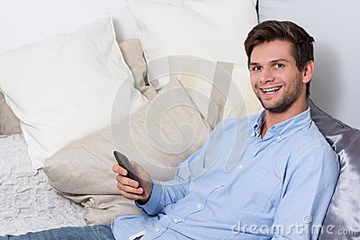 Young man using cellphone on couch