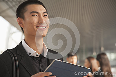 Young Man Using Digital Tablet on Train Platform