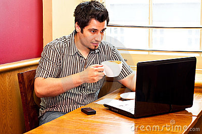 Young man using a laptop and drinking cappuccino