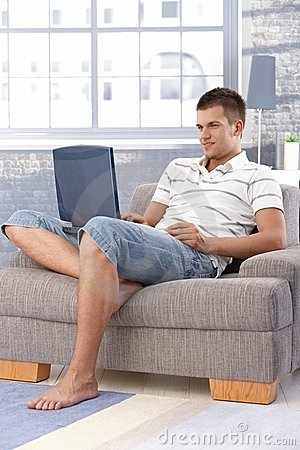 Young man using laptop at home smiling
