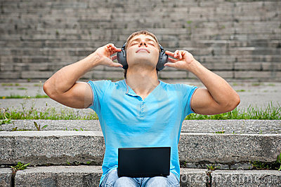 Young man using a laptop and listening music