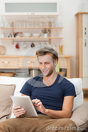 Young man using a tablet at home