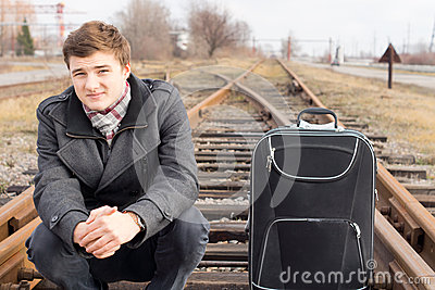 Young man waiting at a rural siding for a train