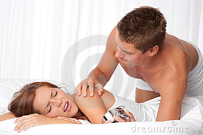 Young man waking up woman in white bed