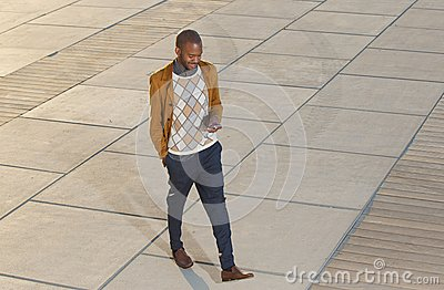 Young man walking and sending message on mobile phone