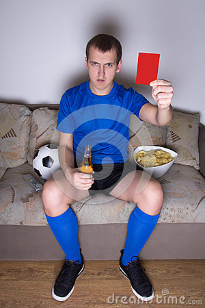 Young man watching football on tv at home and showing red card