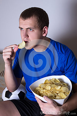 Young man watching soccer on tv at home and eating chips