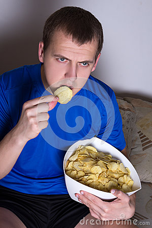 Young man watching tv at home and eating chips