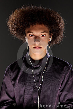 Young man wears music ear plugs and big afro hair