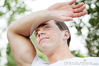 Young man wiping sweaty brow