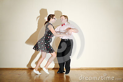 Young man and woman in dress dance at boogie-woogie party.