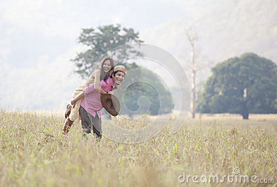 Young man and woman with happy emotion playing on field