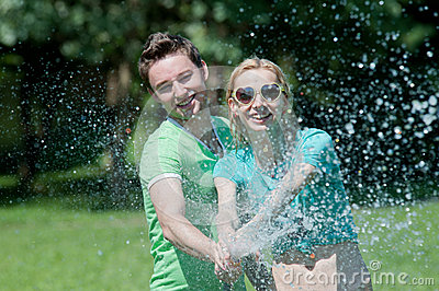 Young man and woman playing with water spray